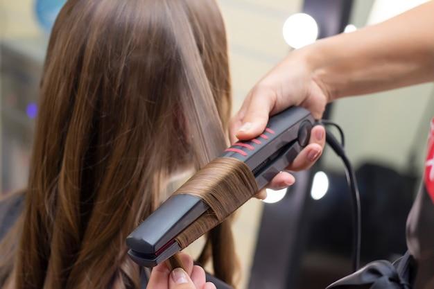 Salon de coiffure pour femmes, salon de beauté. le coiffeur fait des boucles avec un fer à friser