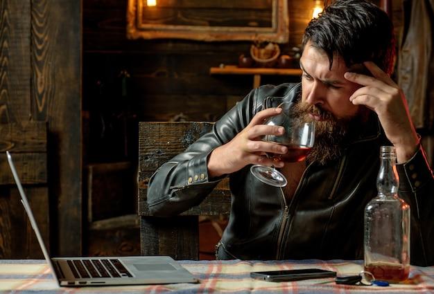 Salon de coiffure, rasage. macho boit près de son ordinateur portable. en pensant. considérer de nouvelles idées