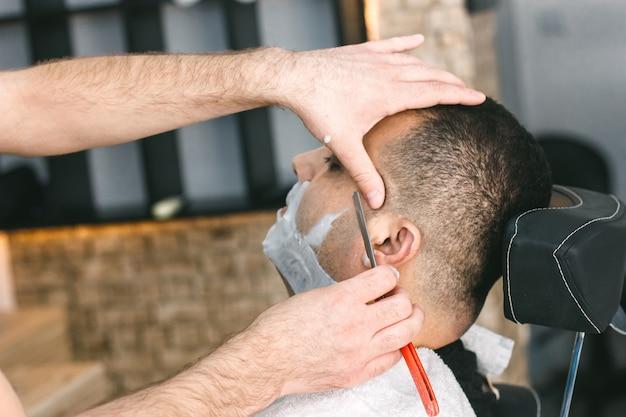 Salon de coiffure rase une barbe à un homme avec un rasoir dans le salon de coiffure