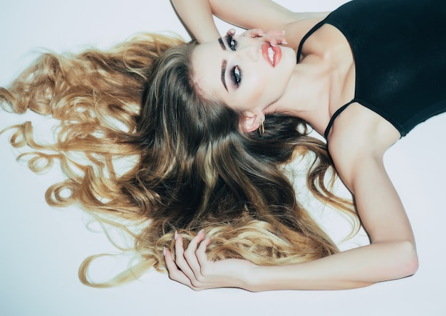 Salon de coiffure et soins capillaires fille sexy aux longs cheveux bouclés en studio blanc