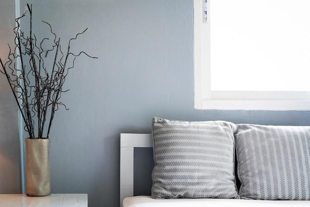 Salon confortable, oreiller gris sur canapé avec fenêtre, espace copie.