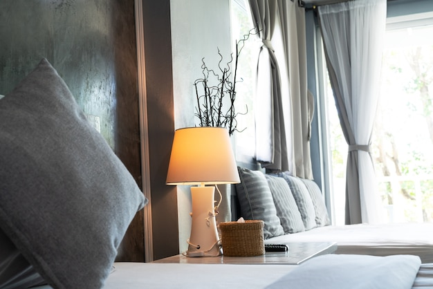 Salon confortable, oreiller gris et lampe de bureau