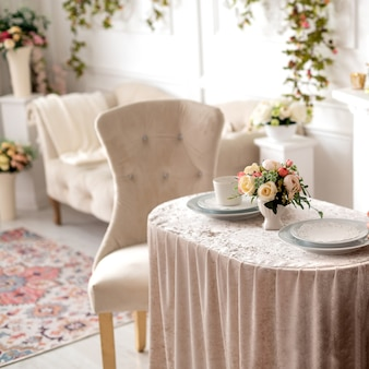 Salon décoré dans un style classique avec des chaises anciennes et une table basse décorée avec un arrangement floral