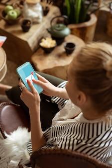 Salon élégant. dame ciblée en veste rayée recevant un message sur son smartphone en attendant son tour dans un salon