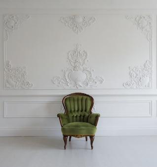 Salon avec fauteuil vert élégant et ancien sur un mur blanc de luxe moulures en stuc bas-relief éléments roccoco