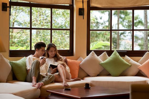 Salon avec fenêtres panoramiques et couple romantique assis sur un grand canapé, lisant un livre ensemble