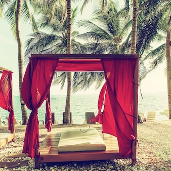 Salon de gazebo romantique au complexe tropical. lits de plage parmi les palmiers. image filtrée
