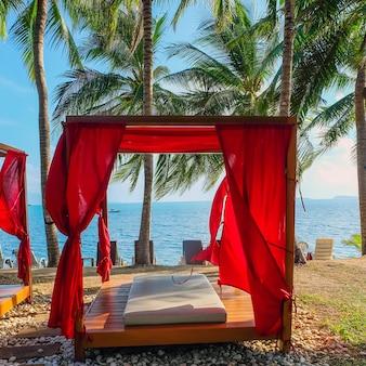 Salon de gazebo romantique au complexe tropical. lits de plage parmi les palmiers.