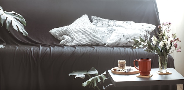 Salon intérieur confortable avec un canapé noir et un vase de fleurs