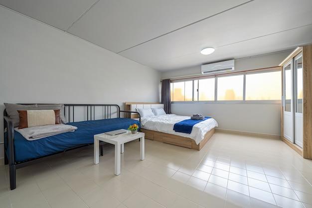 Salon intérieur de luxe avec canapé-lit et lit queen size, table à manger, climatiseur