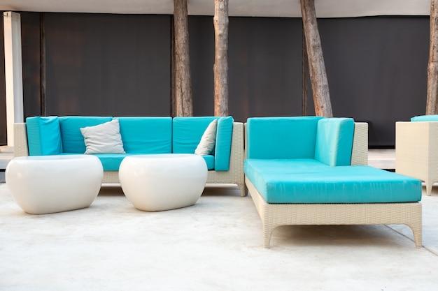 Salon de jardin en rotin blanc avec coussin bleu sur la terrasse du complexe.