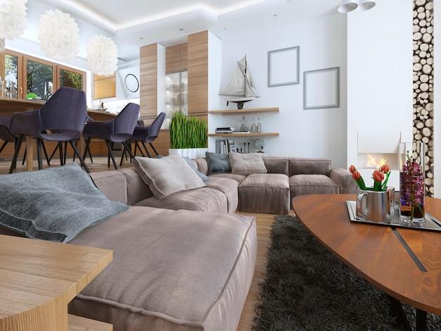 Salon moderne dans un style loft et se fondant en douceur dans la cuisine salle à manger avec grand canapé d'angle et grande cheminée haute avec bois de chauffage.