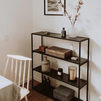 Salon nordique scandinave moderne avec de beaux détails tels que des étagères noires, des vases, des cadres, des cercueils en bois, du coton, une chaise en bois beige, une table blanche