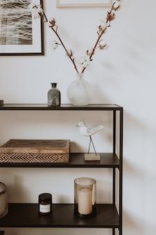 Salon nordique scandinave moderne avec de beaux détails tels que des étagères noires, des vases, des cadres, des cercueils en bois, du coton.
