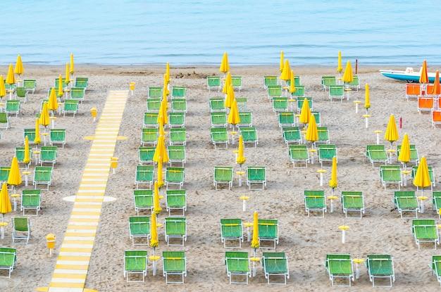 Salon de plage avec parasols jaunes et transats verts sur la côte italienne.