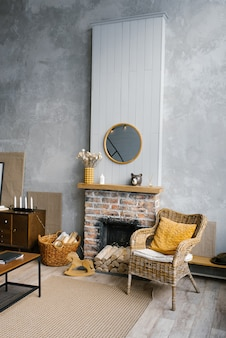 Un salon scandinave aux couleurs gris et or de 2021. l'intérieur d'une maison de campagne avec cheminée et chaise en osier