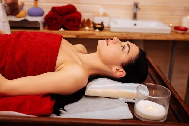 Salon spa professionnel. femme aux cheveux noirs paisible recouverte d'une serviette rouge reposant sur une table en bois dans une armoire de massage