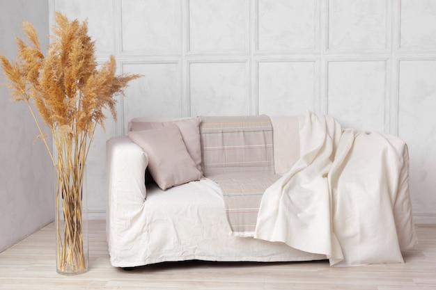 Salon de style scandinave avec canapé en tissu, oreillers, plaid et plante dans un vase sur fond de mur gris