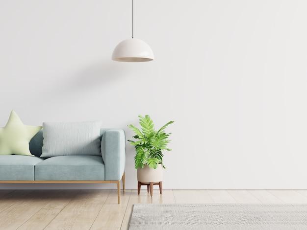 Salon vide avec canapé bleu, plantes et table sur fond de mur blanc vide.