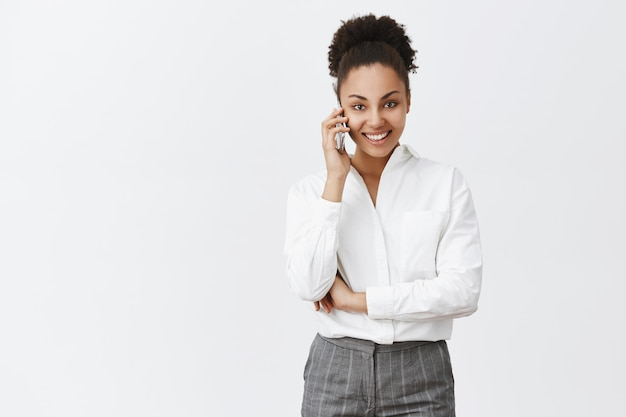 Salut comment allez-vous. portrait de charmante femme d'affaires à la peau sombre confiante en costume, tenant le smartphone près de l'oreille et regardant avec un sourire assuré, prise de rendez-vous sur un mur gris