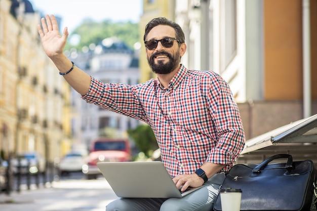 Salut. joyeux bel homme assis dans la rue tout en utilisant son ordinateur portable