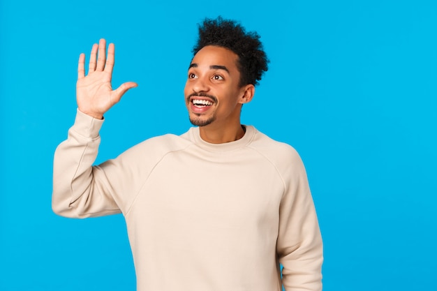 Salut, par ici. attrayant amical afro-américain hipster guy coupe de cheveux afro, moustache, voir un ami dans la foule, en regardant le coin supérieur gauche, en agitant la main en salut, souriant, fond bleu
