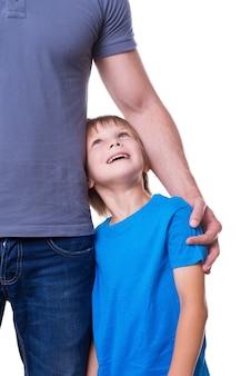Salut! père et fils se tenant près l'un de l'autre tandis que l'enfant regarde et sourit