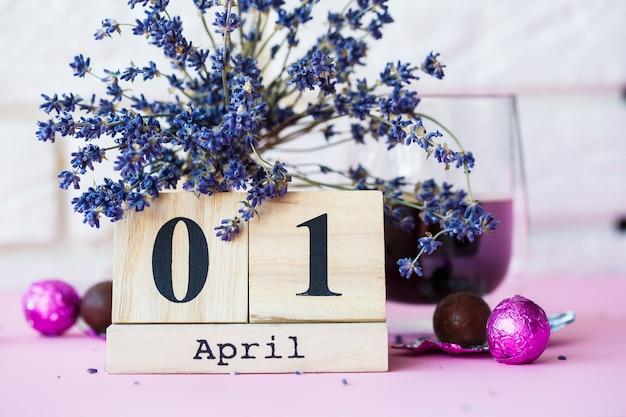 Salut printemps. calendrier en bois avec date 1 avril, sur fond rose. journée mondiale du rire