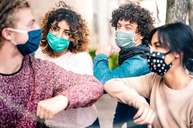 Salutation d'amis multiraciaux avec bosse de coude portant une protection du visage - focus sur la femme de gauche