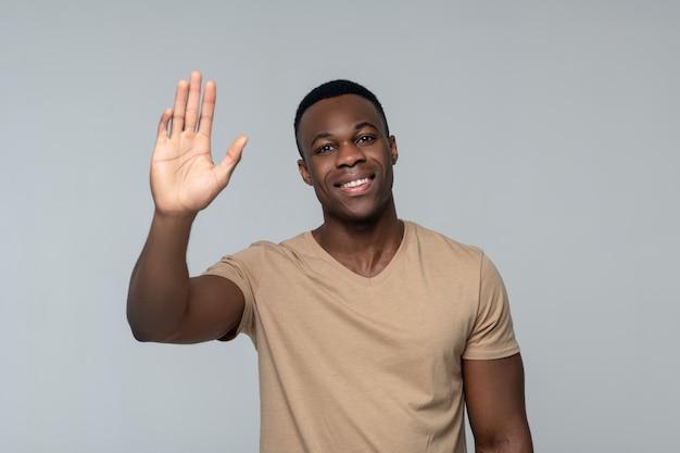 Salutation. heureux souriant jeune homme à la peau sombre, levant la main en salutation debout isolé sur fond gris clair