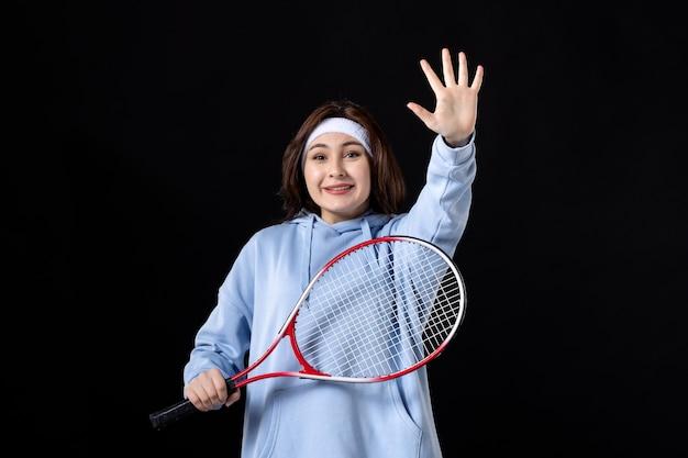 Salutation jeune femme avec raquette sur fond noir