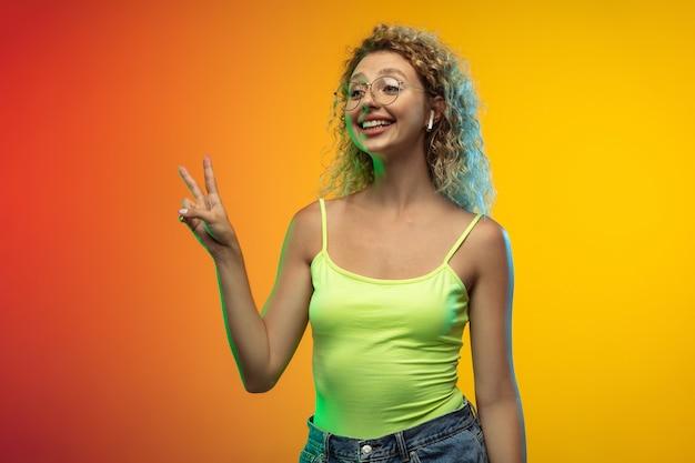 Salutation. portrait de jeune femme caucasienne isolé sur fond de studio dégradé en néon. beau modèle féminin bouclé dans un style décontracté. concept d'émotions humaines, expression faciale, jeunesse, ventes, publicité.