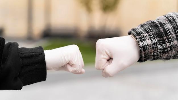Salutations alternatives touchant presque les bosses du poing avec des gants