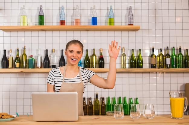 Salutations amicales. belle femme sympathique ravie debout au comptoir et agitant sa main tout en saluant un client