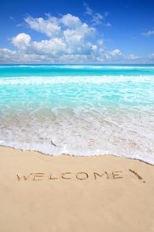 Salutations bienvenus sort de plage écrit sur le sable