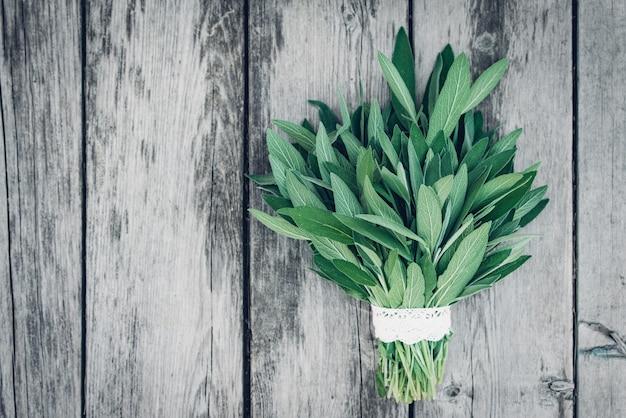 Salvia officinalis. feuilles de sauge sur une vieille table en bois. sauge du jardin. dentelle à la main. photo de magazine rétro. espace de copie.
