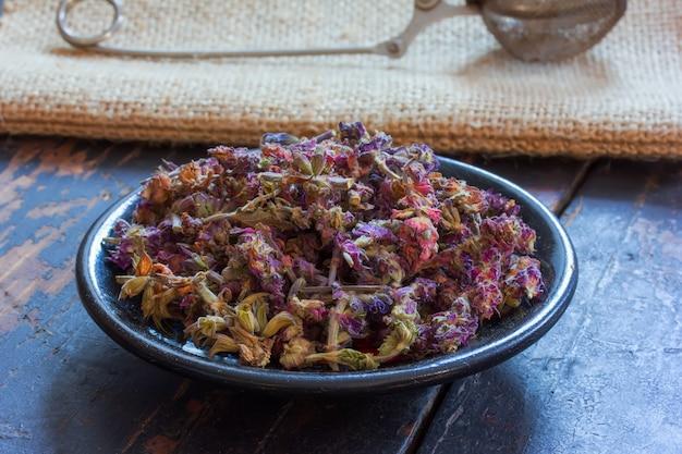 Salvia officinalis sur une soucoupe noire et une passoire à thé pour brasser le thé sur le tapis sur la table noire