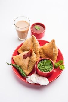 Samosa - pâtisserie frite / cuite au four en forme de triangle avec garniture savoureuse, collations indiennes populaires à l'heure du thé, servies avec du chutney vert, du ketchup aux tomates