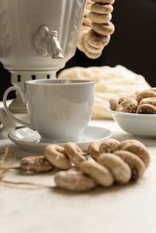Un samovar avec bagels et thé chaud sur la nappe blanche