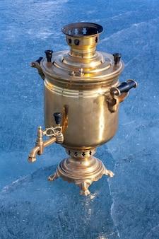 Le samovar rétro se dresse sur de la glace en cuivre et laiton