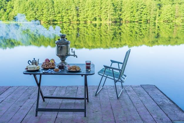 Samovar de thé en métal vintage avec de la fumée blanche et de la nourriture sur la table près du lac d'eau calme dans la forêt verte le matin, en ukraine. concept de nourriture naturelle