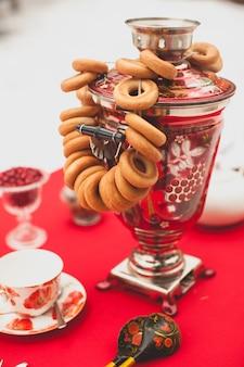 Samovar traditionnel russe en laiton peint sur une nappe rouge, symbole de l'hospitalité. des bagels croustillants, du séchage ou des bagels sont suspendus au samovar