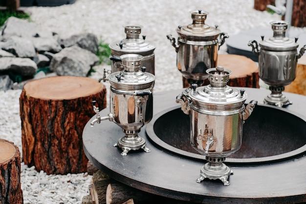 Samovars en cuivre antique sur surface ronde avec des souches en bois en plein air