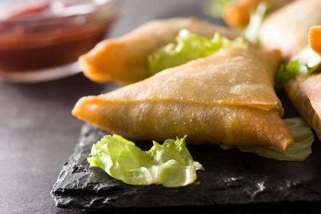 Samsa ou samosas avec viande et légumes sur fond noir. fermer