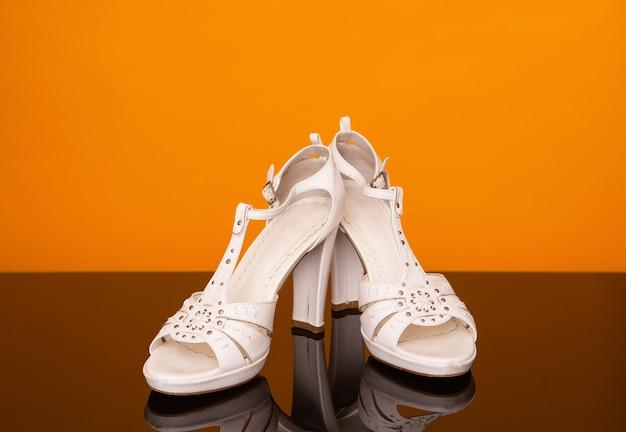 Sandales blanches à talons hauts sur table en verre noir et jaune
