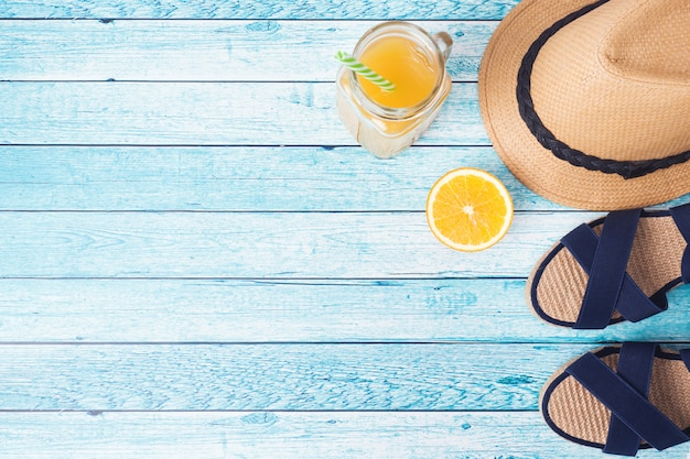 Sandales bleues, chapeau et jus d'orange sur fond bleu