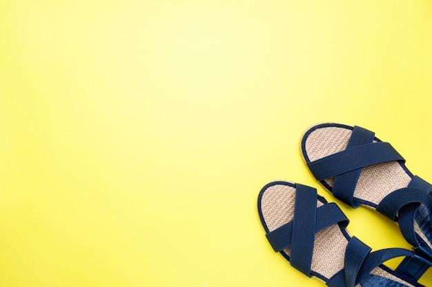Sandales bleues sur fond jaune avec espace de copie. concept vacances d'été. pose à plat