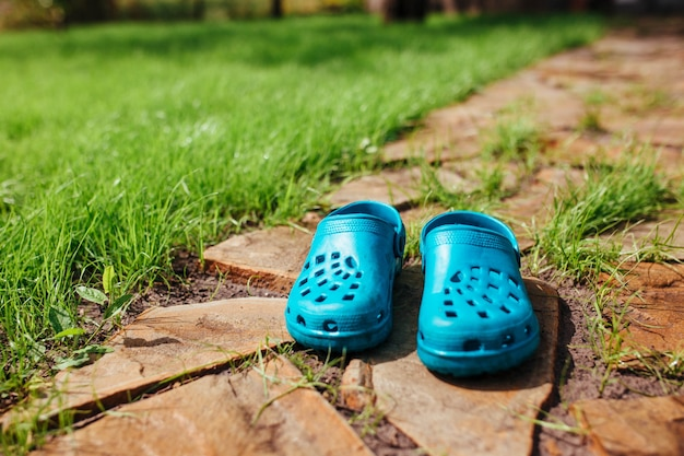 Des sandales en caoutchouc se tiennent sur l'allée du jardin près de la pelouse