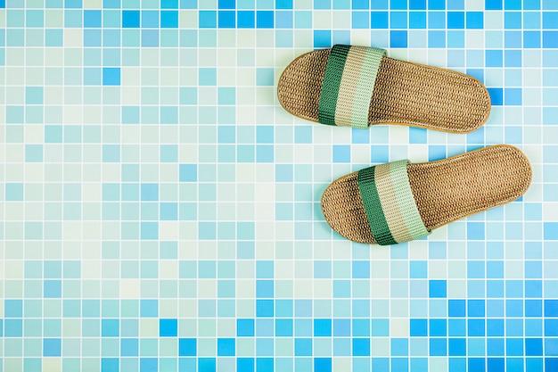 Sandales sur des carreaux de céramique bleue à la piscine.