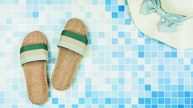 Des sandales et un chapeau de plage sur des carreaux de céramique bleus au bord de la piscine.